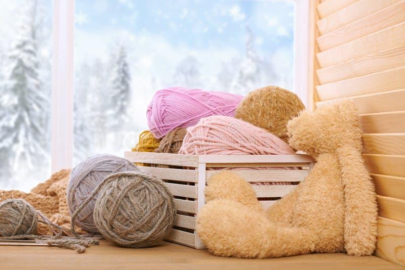 Woolen garn och tyg på fönsterfönsterbrädan Den härliga sikten utanför fönstret - övervintra landskap och snö royaltyfria foton