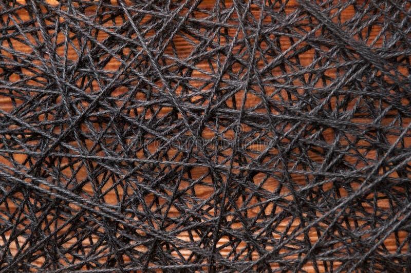 Woolen gesponnene Garne, woolen gesponnene Garne zwischen Eisennägeln, woolen gesponnene Garne zwischen Eisennägeln auf einem Hol lizenzfreies stockbild