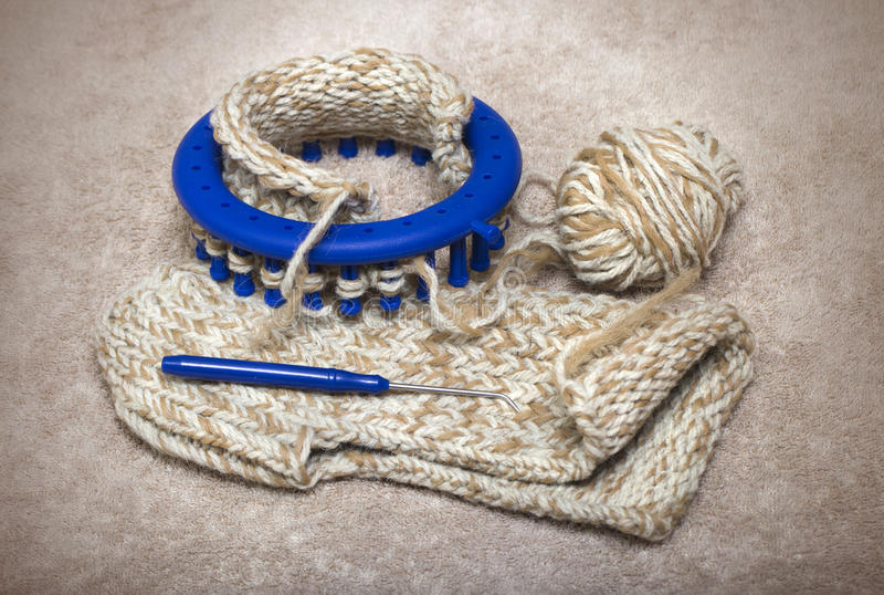 Woolen häftklammermatare som stickas från två garner på en rund vävstol arkivbilder