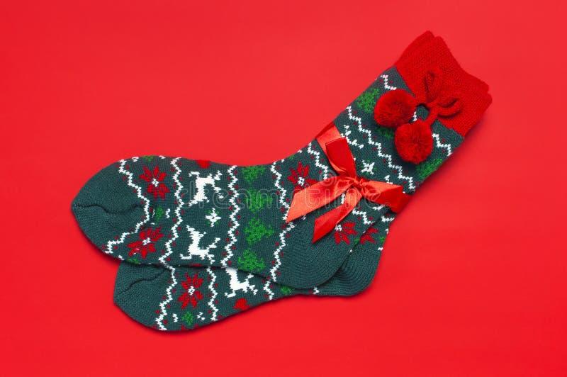 Woolen Socken mit einer Verzierung des Weihnachtsneuen Jahres auf roter flacher Lage der Draufsicht des Hintergrundes Feiertagsko lizenzfreie stockfotografie