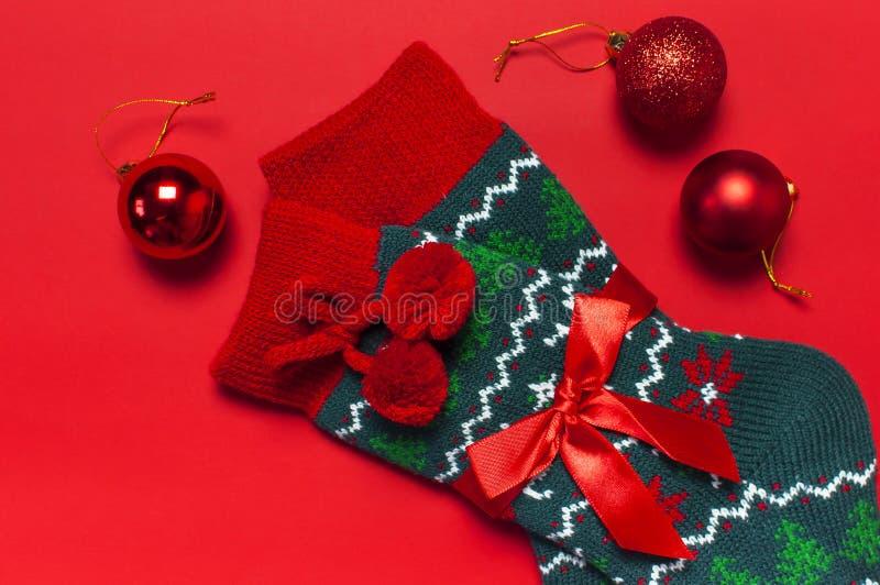 Woolen Socken mit einer Verzierung des Weihnachtsneuen Jahres auf roter flacher Lage der Draufsicht des Hintergrundes Feiertagsko stockfoto