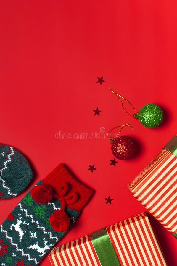 Woolen Socken mit einer Verzierung des Weihnachtsneuen Jahres auf roter flacher Lage der Draufsicht des Hintergrundes Feiertagsko lizenzfreies stockbild
