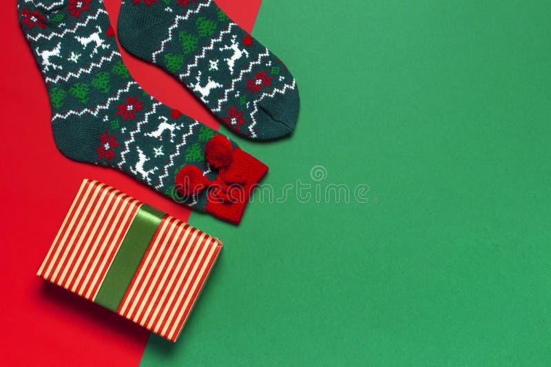 Woolen Socken mit einer Verzierung des Weihnachtsneuen Jahres auf roter flacher Lage der Draufsicht des Hintergrundes Feiertagsko lizenzfreie stockfotos
