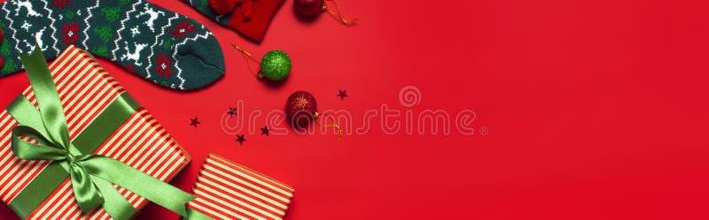 Woolen Socken mit einer Verzierung des Weihnachtsneuen Jahres auf roter flacher Lage der Draufsicht des Hintergrundes Feiertagsko stockfotografie