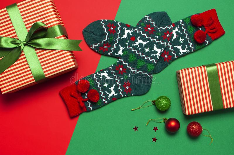 Woolen Socken mit einer Verzierung des Weihnachtsneuen Jahres auf roter flacher Lage der Draufsicht des Hintergrundes Feiertagsko stockbilder