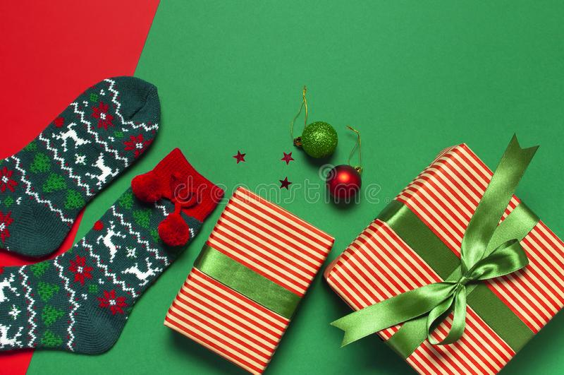 Woolen Socken mit einer Verzierung des Weihnachtsneuen Jahres auf roter flacher Lage der Draufsicht des Hintergrundes Feiertagsko stockfotos
