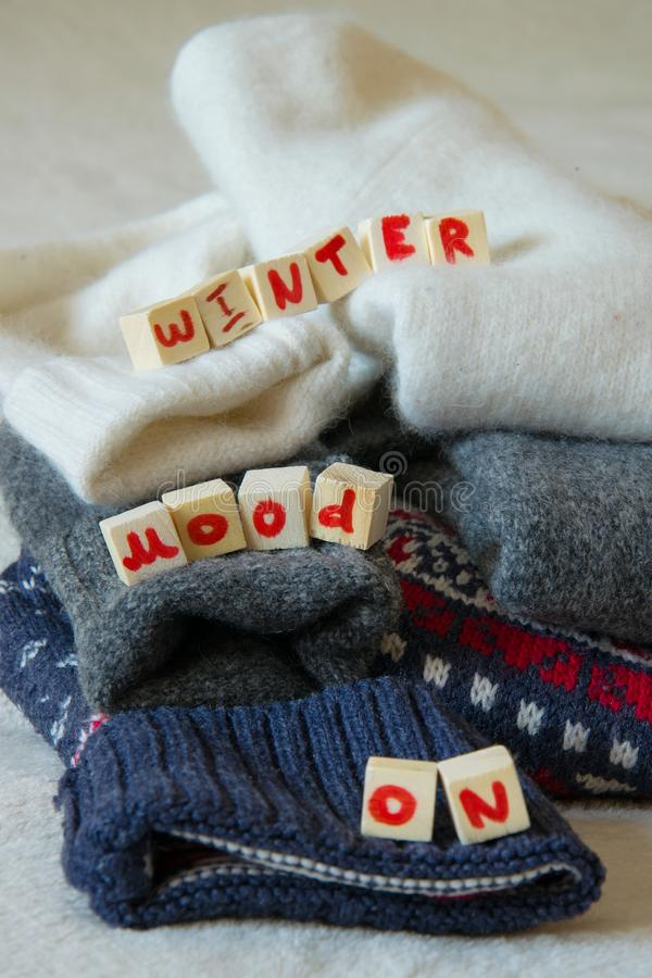Woolen sweaters with `Winter mood ON` text stock photos