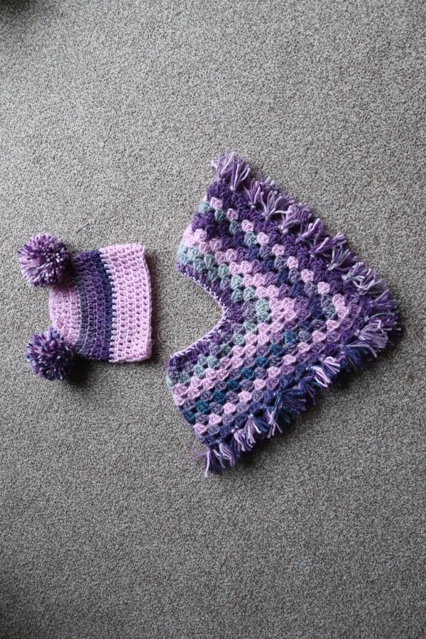 Baby crochet poncho and hat. Woollen yarn used to make baby clothing .poncho and hat in purple wooden yarn royalty free stock image