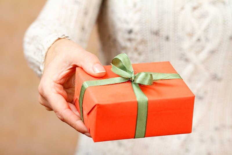 Wooman jugeant un boîte-cadeau attaché avec le ruban vert dans la main images libres de droits