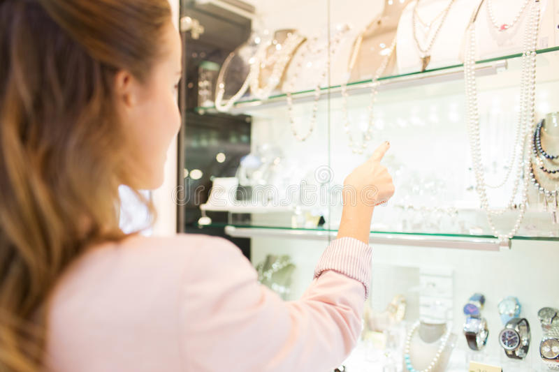 Wooman pointing finger to window at jewelry store. Sale, consumerism and people concept - close up of woman pointing finger to shopping window at jewelry store stock image