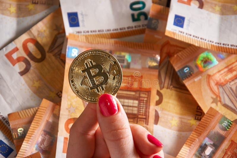 Woomen ` s ręka z bitcoin i 50 pięćdziesiąt euro tła wystawia rachunek banknoty obraz stock