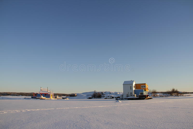 Woonboten dichtbij een eiland op Yellowknife-Baai in Grote Slaaf Lake stock foto's