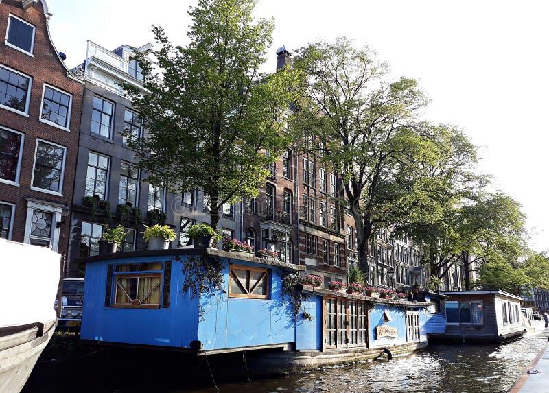 Woonboten, en mooie traditionele huizen langs kanaal in het stadscentrum van Amsterdam, Nederland royalty-vrije stock fotografie