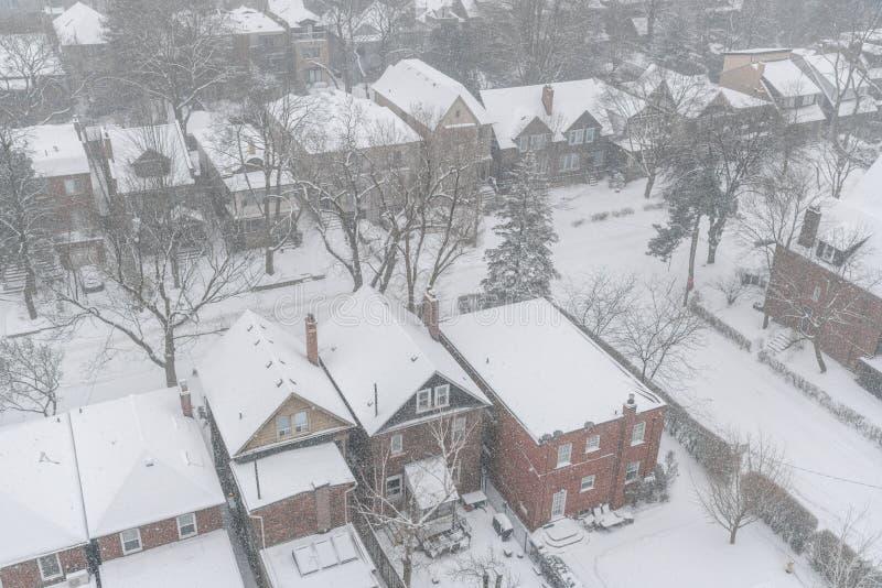 Woondiehuizen en daken met sneeuw in de wintersneeuwstorm worden behandeld in Toronto royalty-vrije stock afbeelding