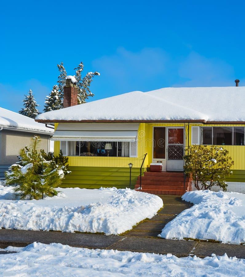 Woonhuis in sneeuw op een zonnige dag op blauwe hemelachtergrond stock afbeeldingen