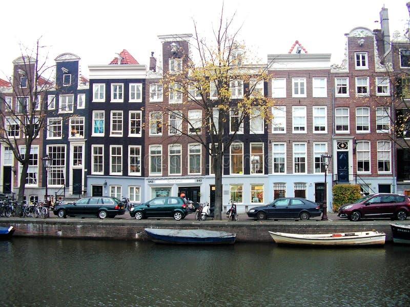 Woonhuizen en boten in Amsterdam stock afbeeldingen