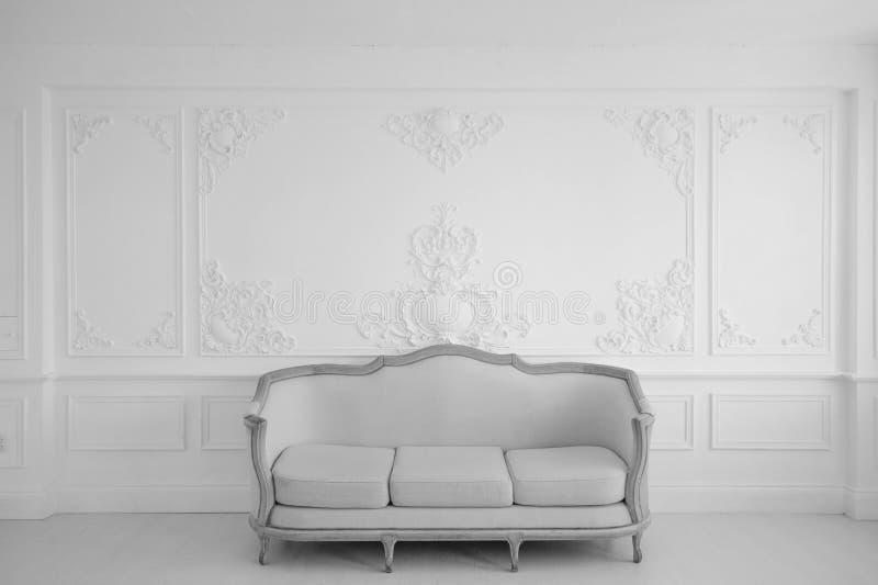 Woonkamer met antieke modieuze lichte bank op van de het ontwerp bas-hulp van de luxe witte muur van de gipspleisterafgietsels ro royalty-vrije stock afbeelding