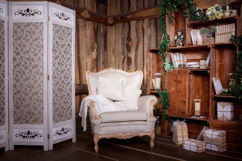 Woonkamer met beige stoel en boekenkast royalty-vrije stock afbeeldingen