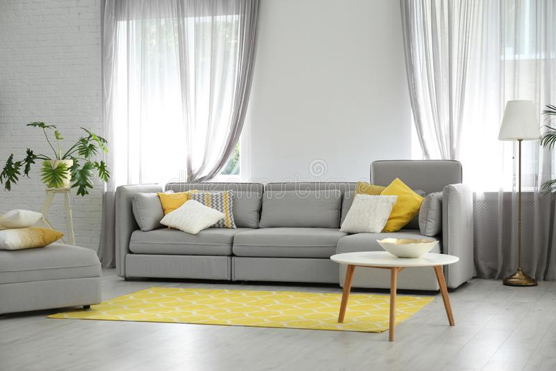 Woonkamer met comfortabele bank en modieus decor stock foto's