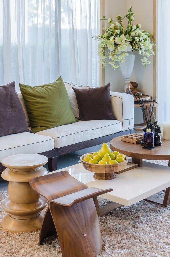 Woonkamer met houten meubilair en bloem stock fotografie