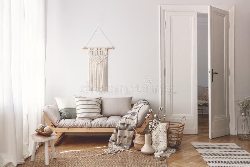 Woonkamer met modieus macramé, bank, houten toebehoren en deuren open aan volgende ruimte royalty-vrije stock foto