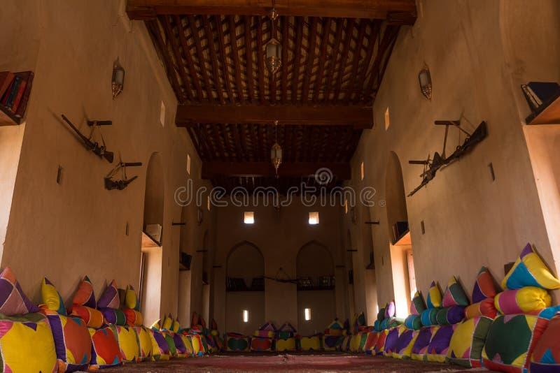 Woonkamer met tapijt, kussens en wapens in Nakhal-Fort stock fotografie