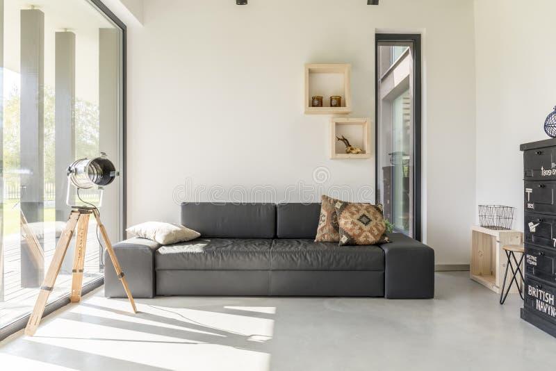 Woonkamer met zwart meubilair stock afbeelding