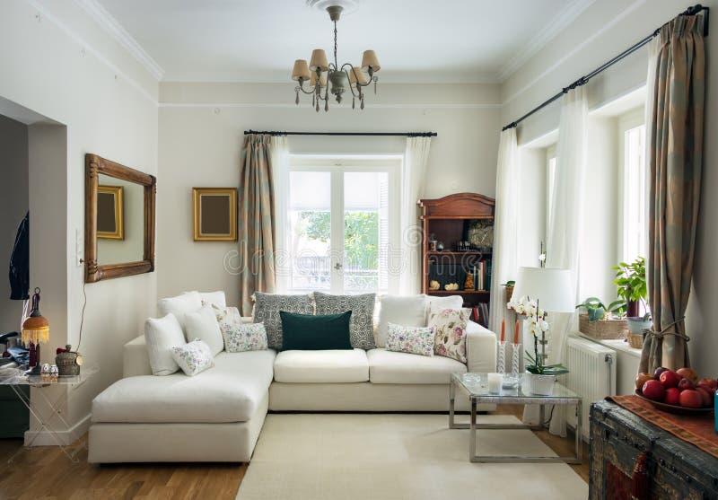 Woonkamer zeer bocht met eiken houten vloer, vier zetelsbank, wit tapijt en retro objets, Griekenland royalty-vrije stock foto