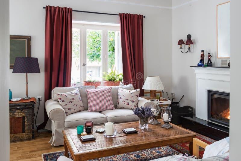 Woonkamer zeer bocht met open haard, eiken houten vloer, rode curtins, een boomstam en retro objets, Griekenland stock fotografie