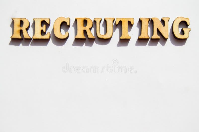 Woord het aanwerven wordt geschreven in houten brieven op een witte achtergrond, het concept het inhuren van werknemers, rekruter stock afbeelding