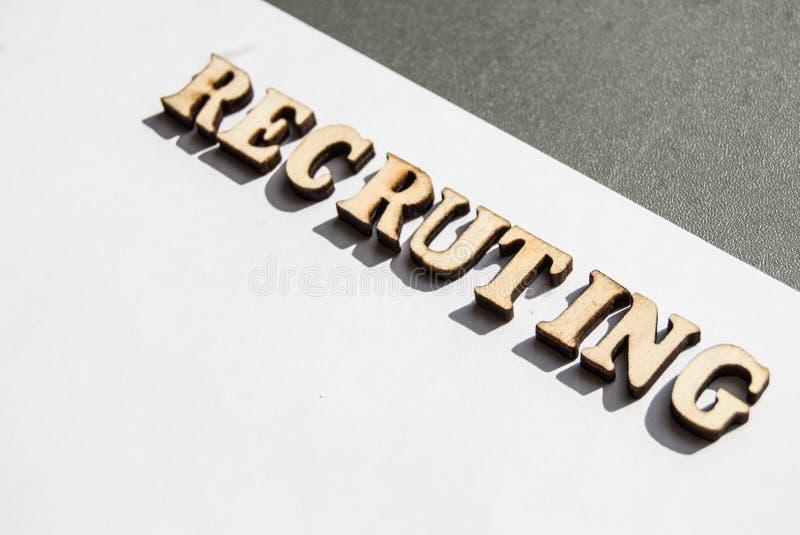 Woord het aanwerven wordt geschreven in houten brieven op een witte achtergrond, het concept het inhuren van werknemers, rekruter stock fotografie