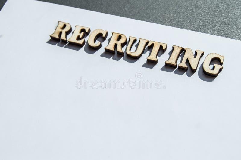 Woord het aanwerven wordt geschreven in houten brieven op een witte achtergrond, het concept het inhuren van werknemers, rekruter stock foto's