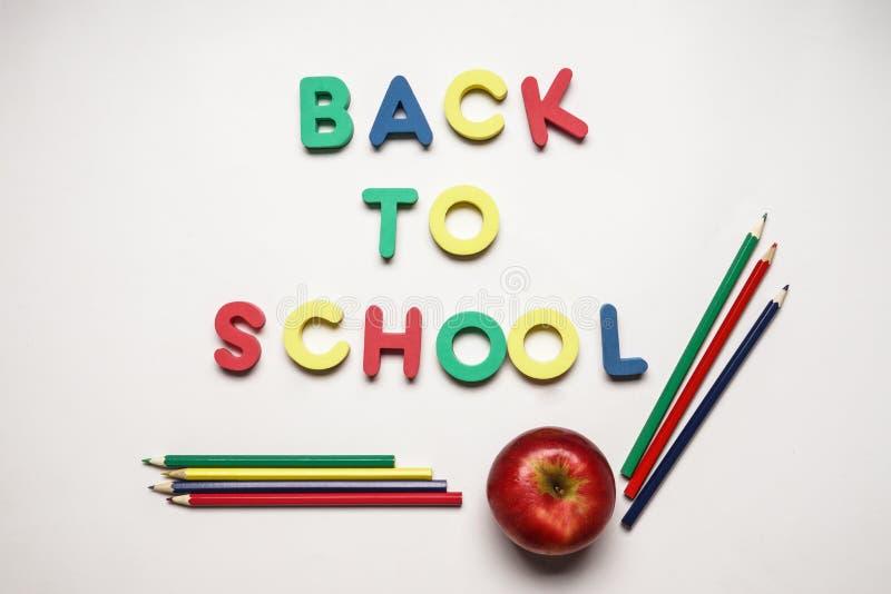 Woorden TERUG NAAR SCHOOL van kleurenbrieven met appel en potloden op witte achtergrond worden gemaakt die stock foto's