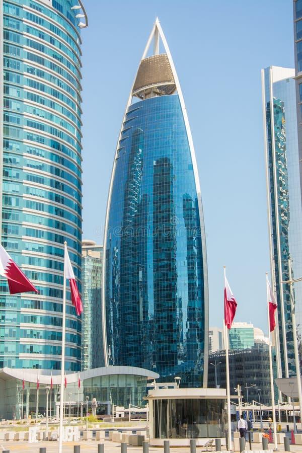 Woqod tornbyggnad i Doha som är qatarisk bland andra skyskrapor royaltyfria foton