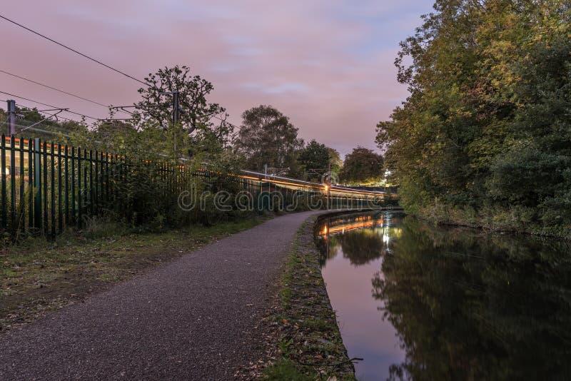 Worcester zu Birmingham-Kanal, in England, Großbritannien Der Fußweg durch die Seite des Kanals, wenn ein Zug vorüber entlang Sei lizenzfreie stockfotos