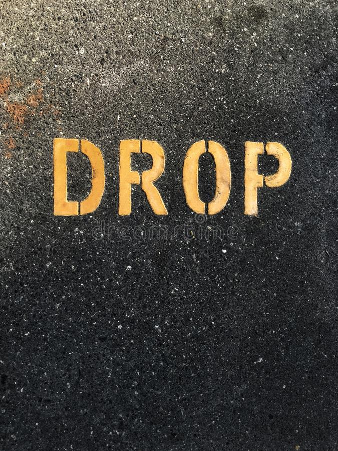 Graphic writing on the asphalt road. Word 'drop' painted in yellow color on the black tar road. Urban traffic signs and symbols royalty free stock photo