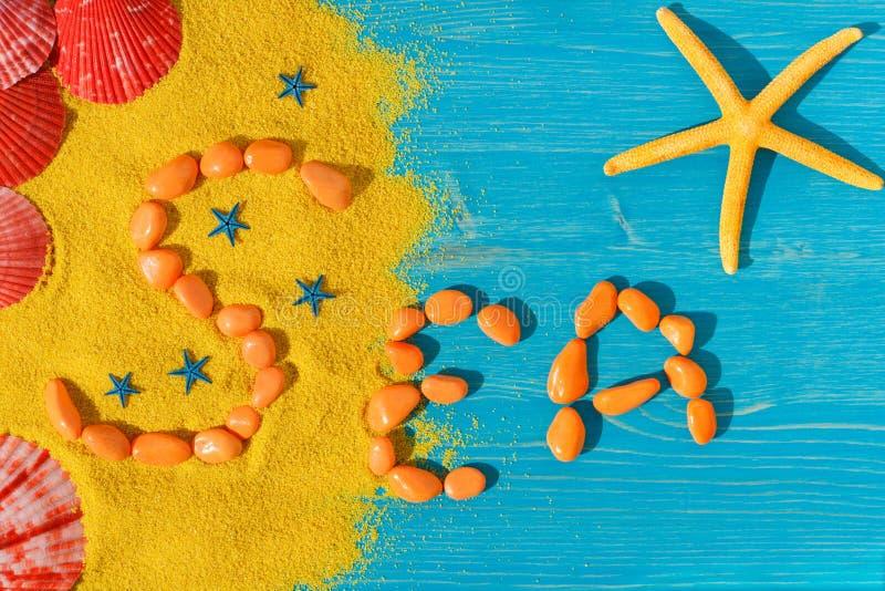 Word 'overzees 'wordt opgemaakt van oranje stenen op een kleurenachtergrond stock afbeeldingen