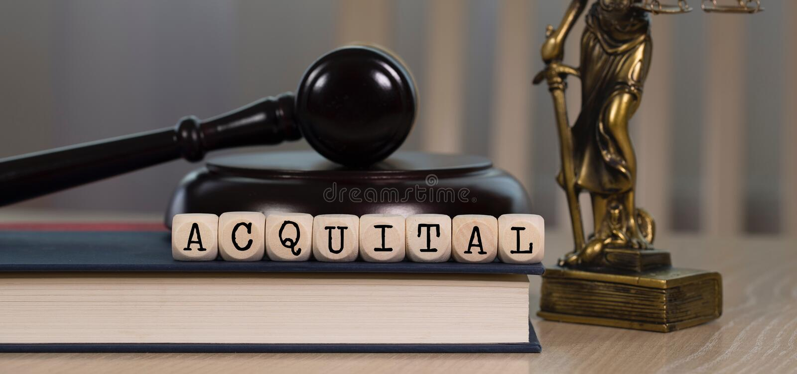 Word ACQUITAL composed of wooden dices. Wooden gavel and statue of Themis in the background royalty free stock image