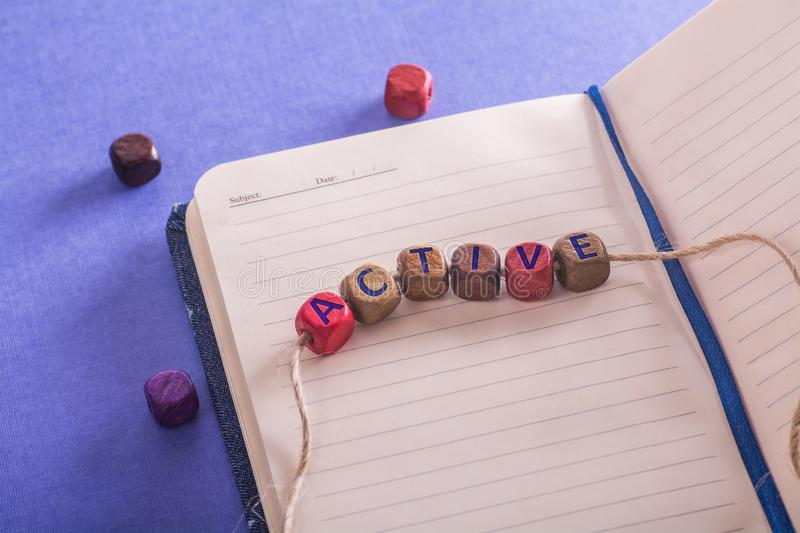 Word active on wooden cubes. Through a rope with notebook on blue paper sheet stock photos