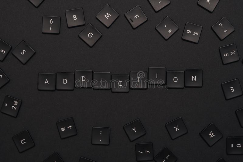 The word `Addiction` assembled from black keyboard keys stock images