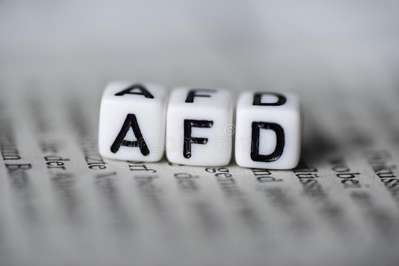 Word AFD formed by wood alphabet blocks on newspaper german party politics royalty free stock images
