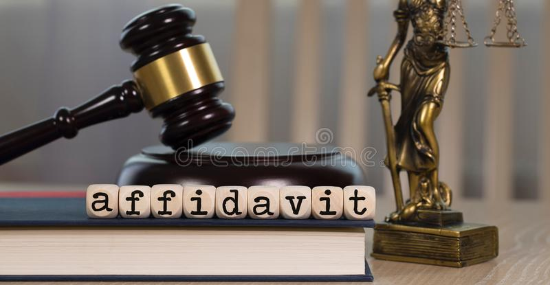 Word AFFIDAVIT composed of wooden dices. Wooden gavel and statue of Themis in the background. Word AFFIDAVIT  composed of wooden dices. Wooden gavel and statue stock photography