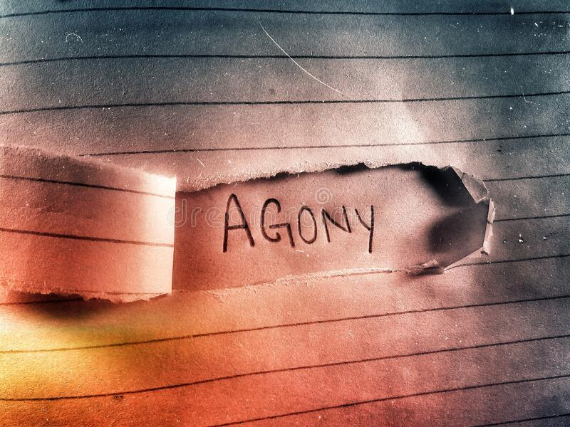 The word agony in simple handwriting fonts on the cut paper page stock images
