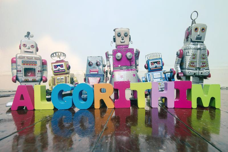The word ALGORITHIM with wooden letters and retro toy robots o royalty free stock images