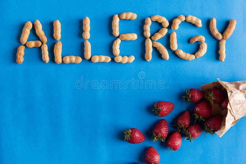 Word allergy signed with peanuts with strawberry. royalty free stock photos