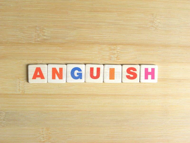 Word Anguish on wood background.  stock photos