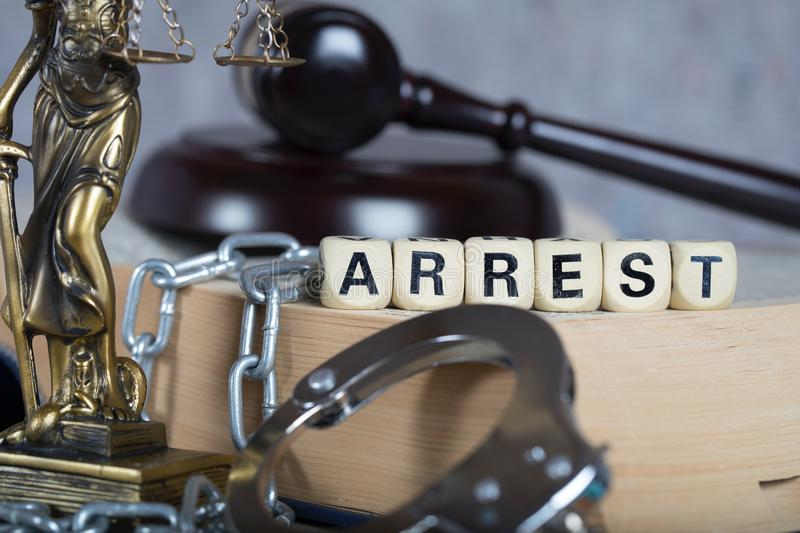 Word ARREST composed of wooden letters. Statue of Themis and judge's gavel in the background royalty free stock image