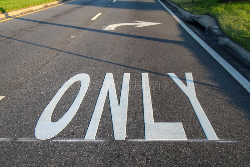 The word `ONLY`, Florida, USA. The word `ONLY` is an arrow painted white indicating right turn on an asphalt street stock images