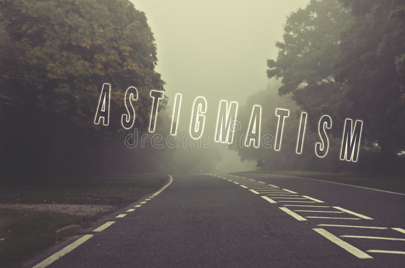 Word astigmatism written on danger road on a foggy day. Road through the autumn forest. Vision problem. stock photo