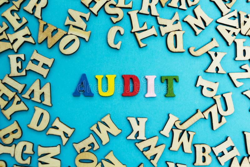 The word `audit` is laid out from multicolored letters on a blue background.  royalty free stock images